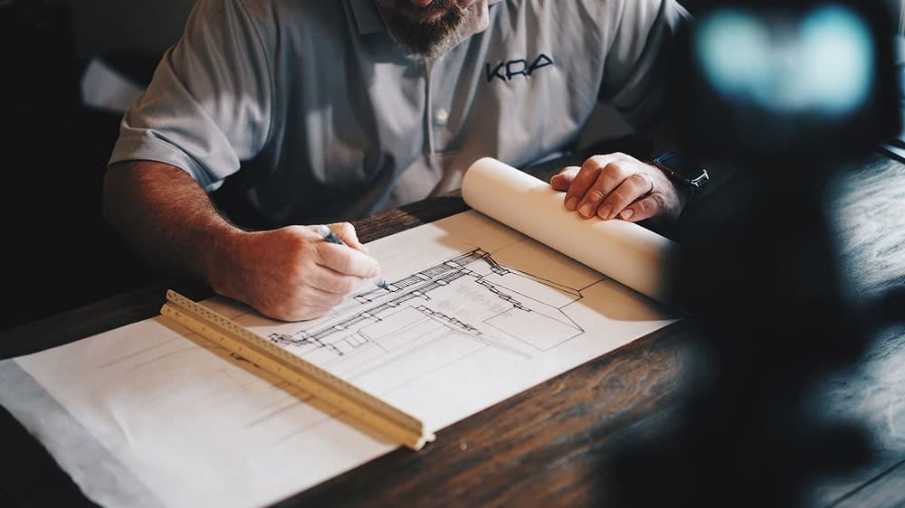 A man sketching home/building blueprint.